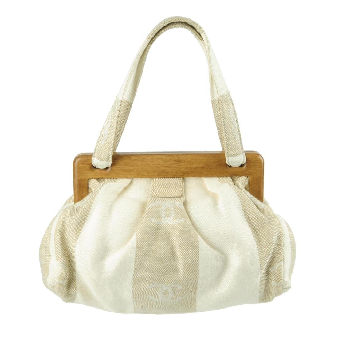 CHANEL - a white and beige canvas handbag. Designed