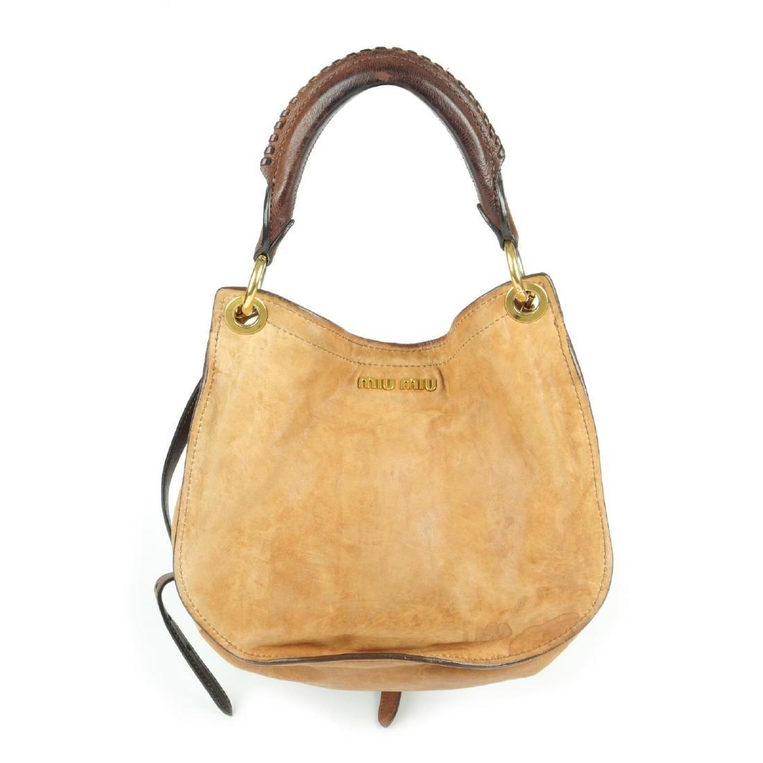 MIU MIU - a leather saddle handbag. Designed with a tan