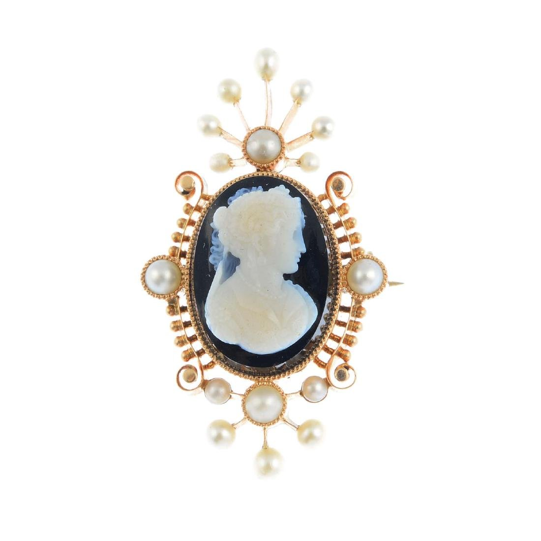 An onyx and split pearl brooch. The oval onyx cameo,