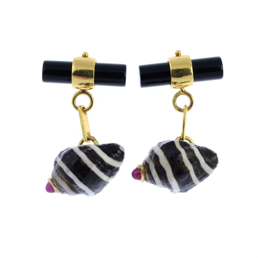A pair of onyx and ruby shell cufflinks. Each designed
