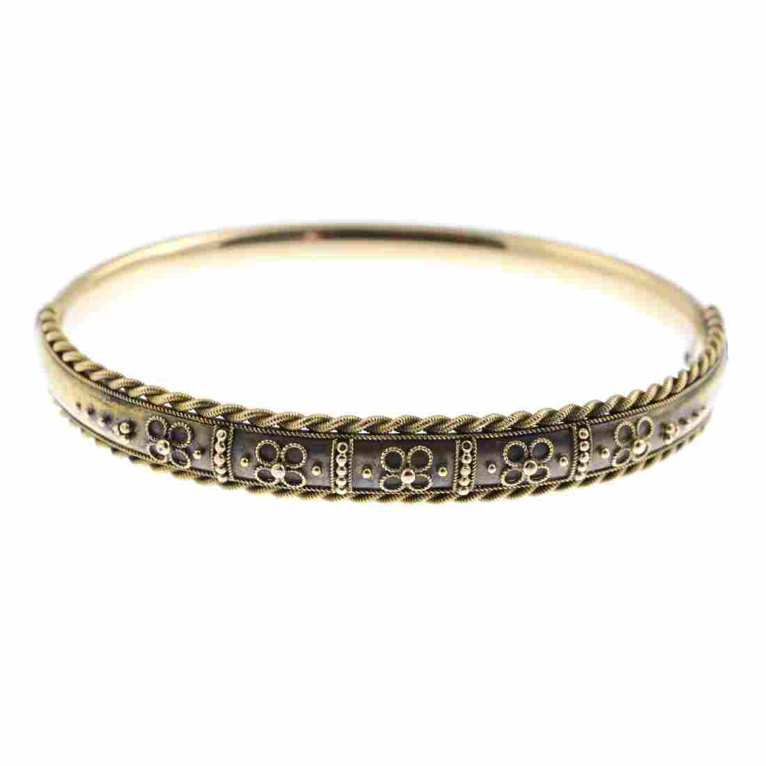 A late Victorian 15ct gold hinged bangle. The floral