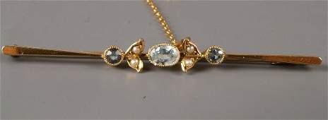 332: 9ct gold three stone aquamarine and seed pearl bar