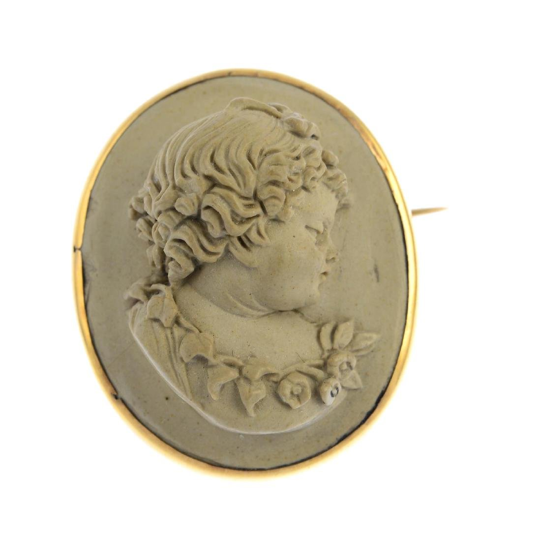 A mid Victorian gold lava cameo brooch. The oval lava