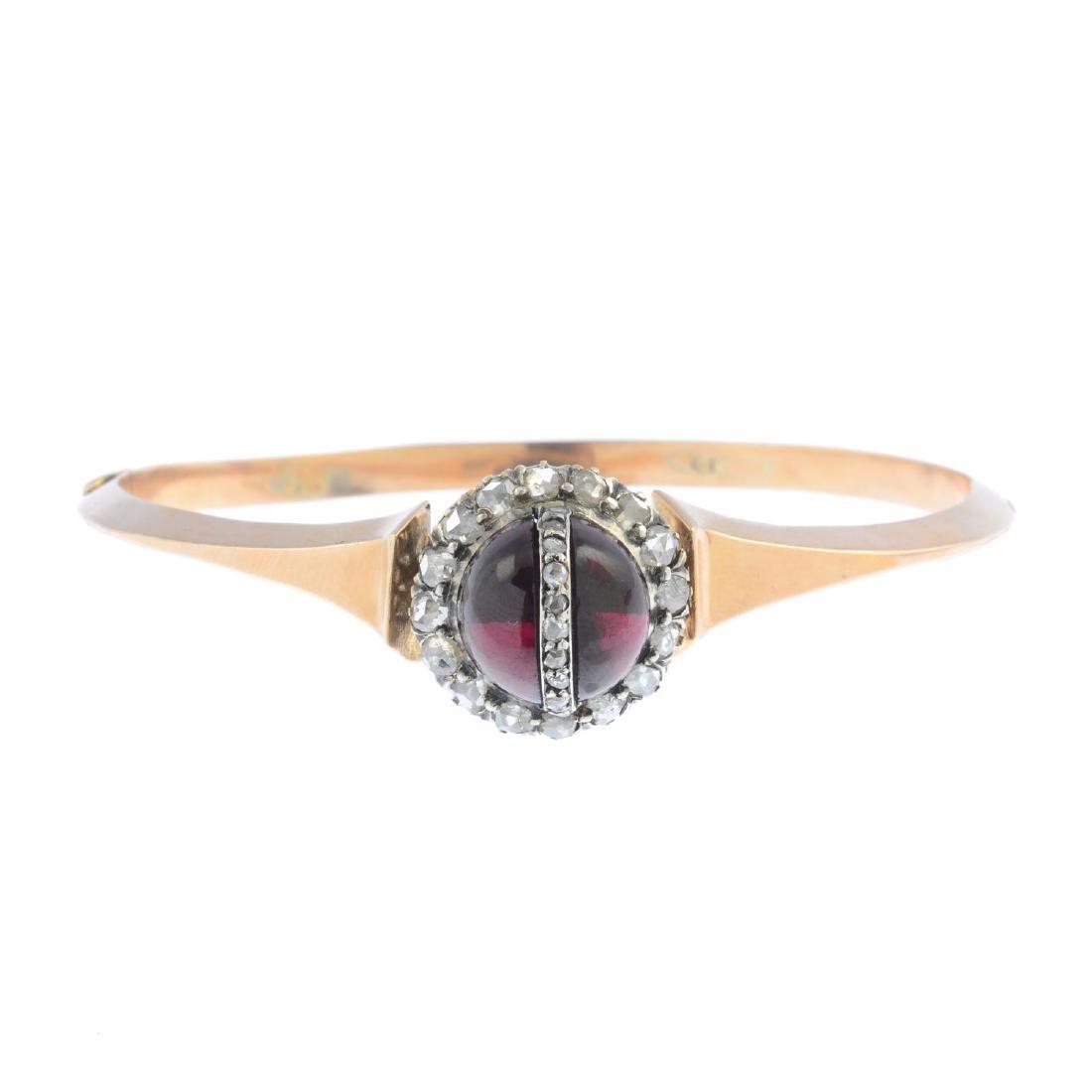 A late Victorian gold garnet and diamond hinged bangle.
