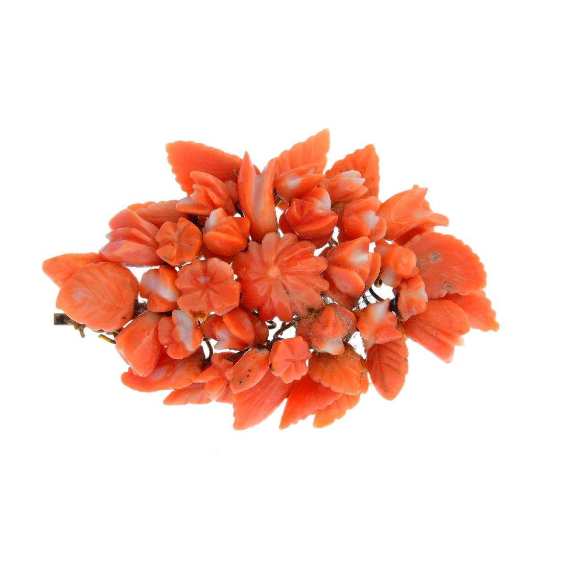 A coral brooch. Of marquise outline, the carved coral