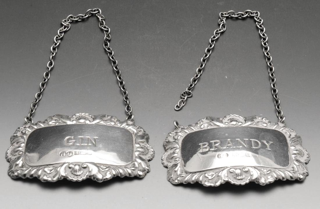 A modern pair of silver wine labels, each of oblong