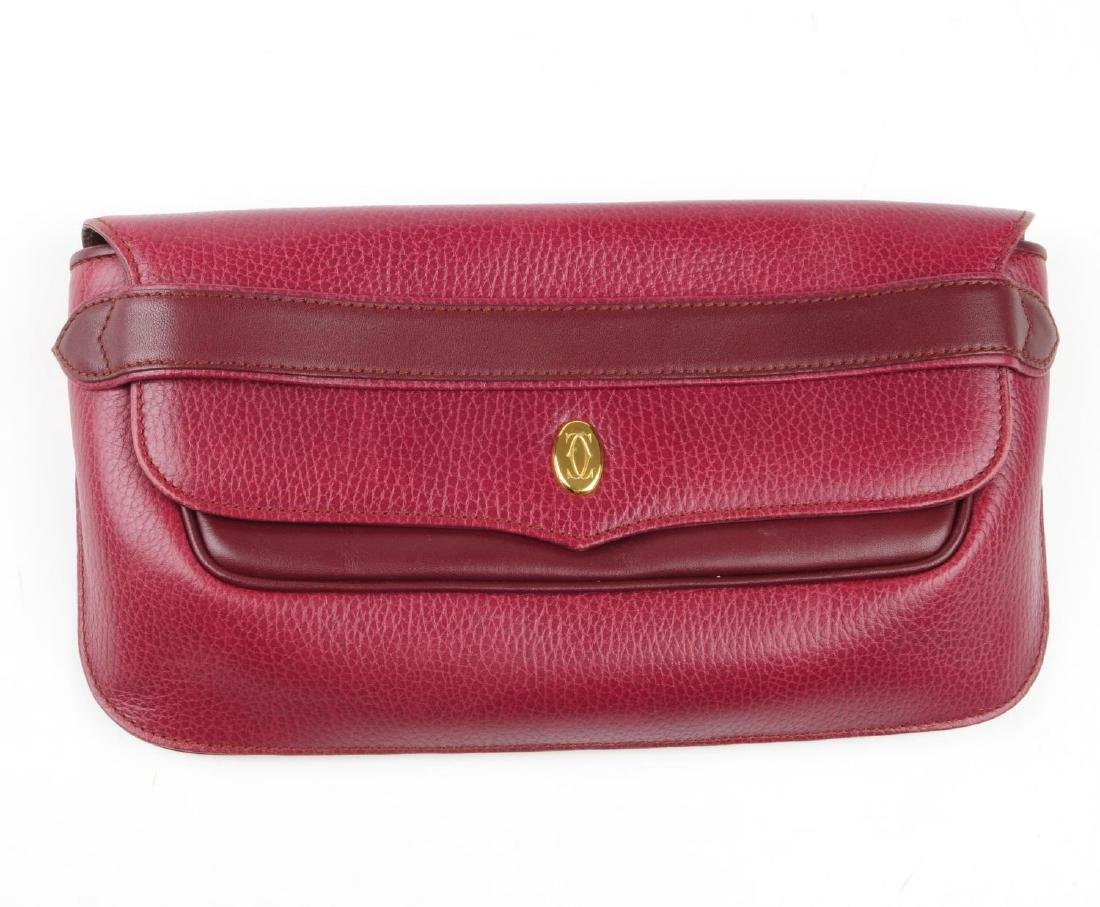 CARTIER - a Bordeaux leather clutch and a pair of - 2