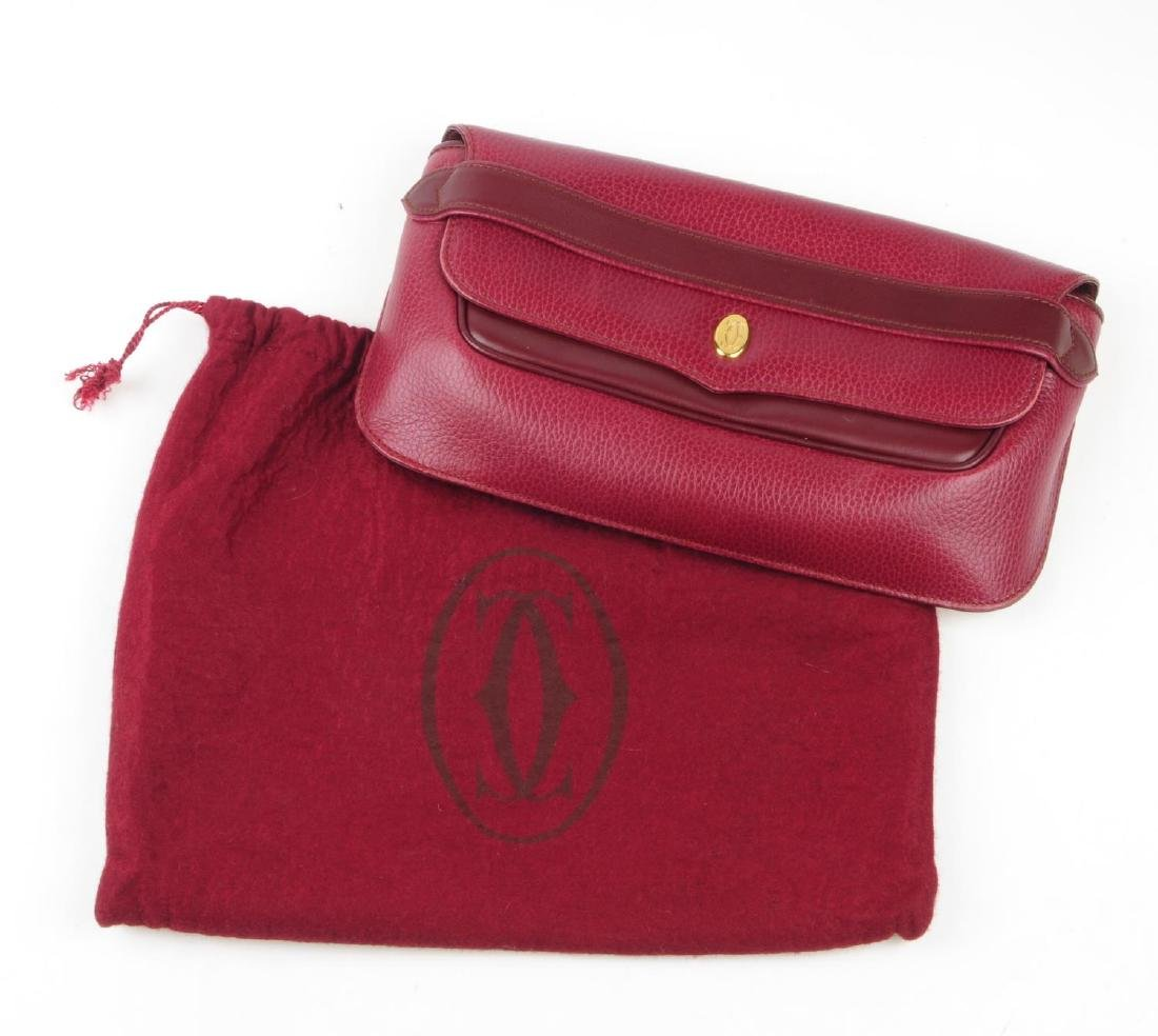 CARTIER - a Bordeaux leather clutch and a pair of - 4