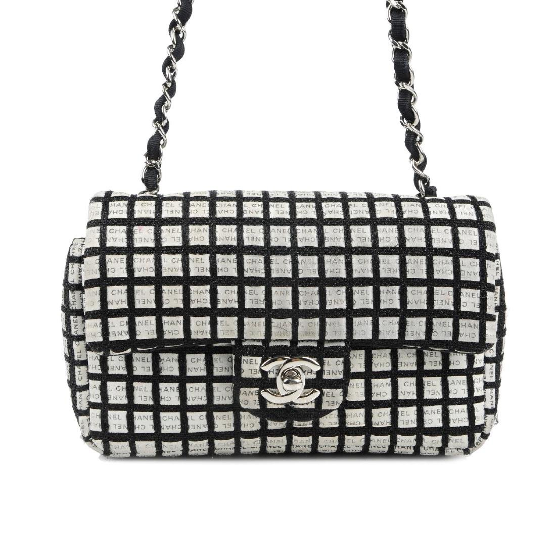 CHANEL - a black and white woven New Mini Flap handbag.
