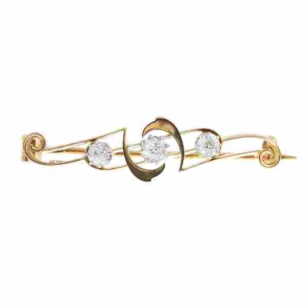 An early 20th century gold diamond three-stone bar