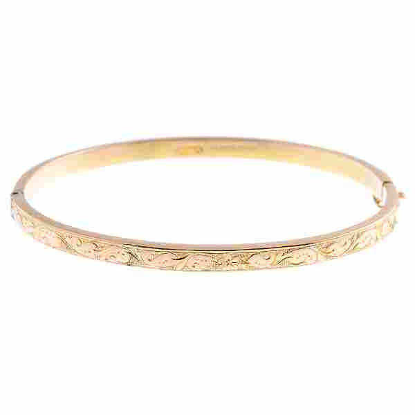 A 9ct gold hinged bangle. The engraved foliate panel,