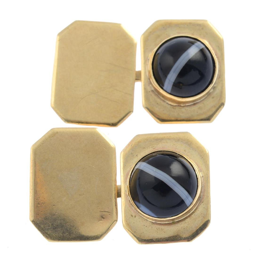 Two pairs of cufflinks. The first pair each designed as