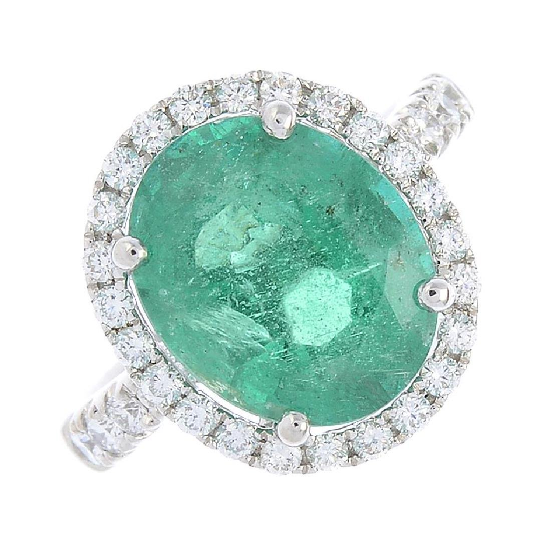 A emerald and diamond dress ring. The oval-shape