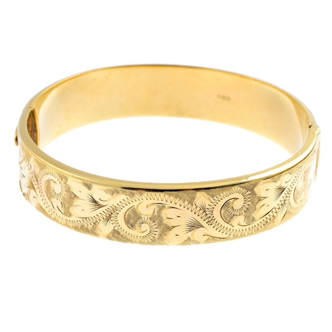 (21770) A 1970s 9ct gold hinged bangle. The scrolling