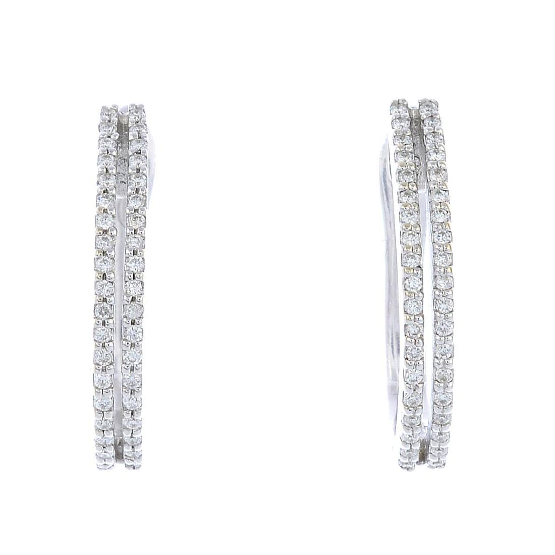 A pair of diamond hoop earrings. Each designed as a