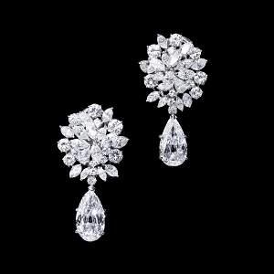 A pair of diamond earrings. Each designed as a