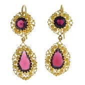 A pair of garnet earrings. Each designed as a