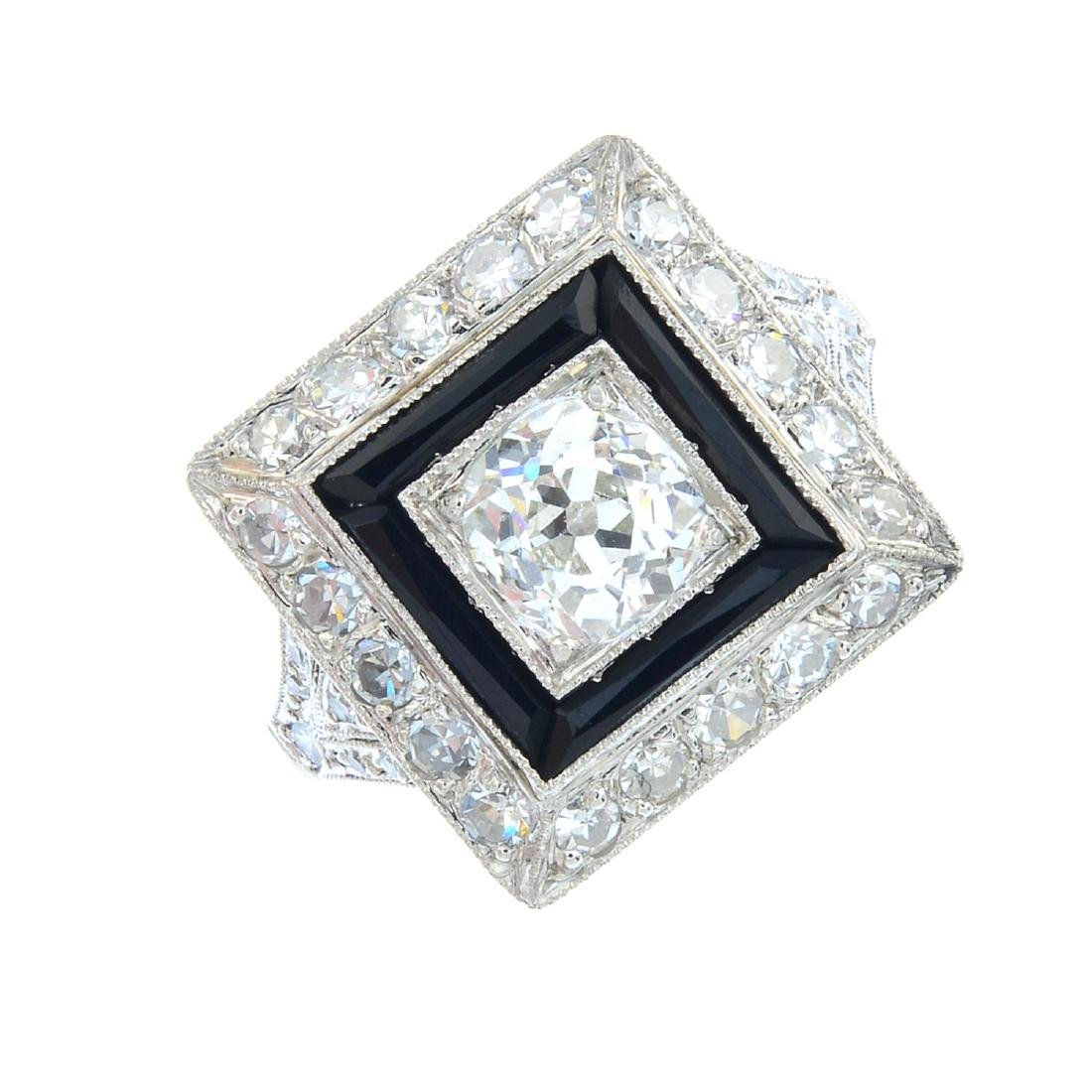 A diamond and onyx dress ring. The old-cut diamond,
