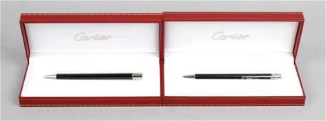 Three Cartier ballpoint pens each having black resin