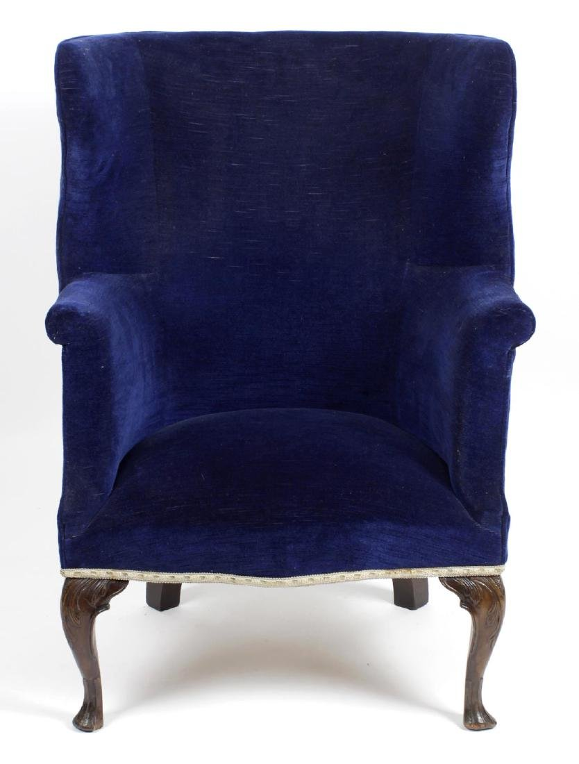An antique wing back arm chair, with blue draylon