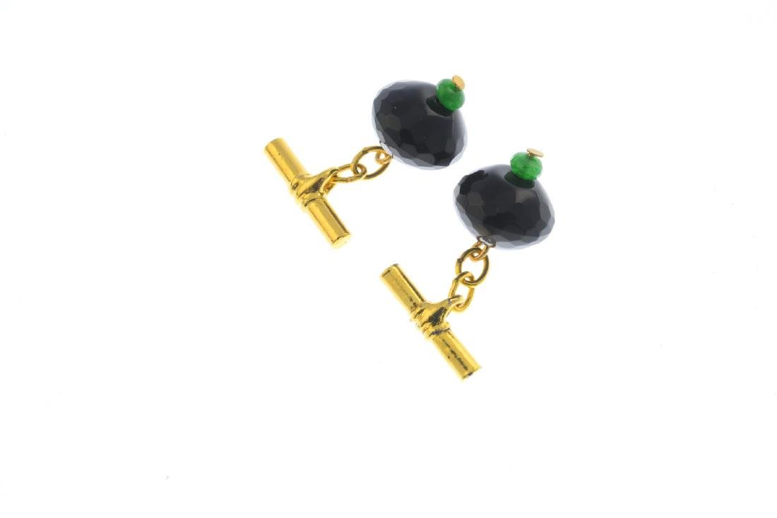 A pair of onyx and emerald cufflinks. Each designed as - 2