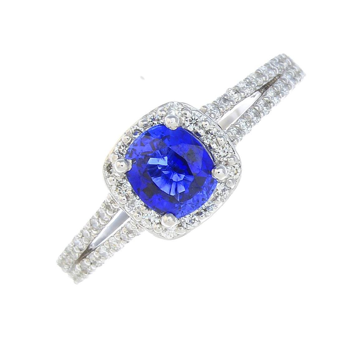 A sapphire and diamond cluster ring. The cushion-shape