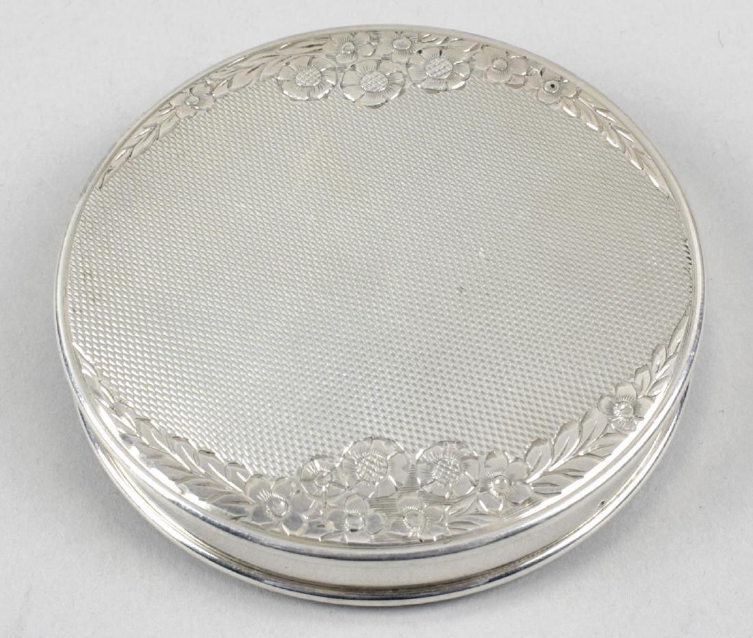 A mid-twentieth century silver circular compact, engine