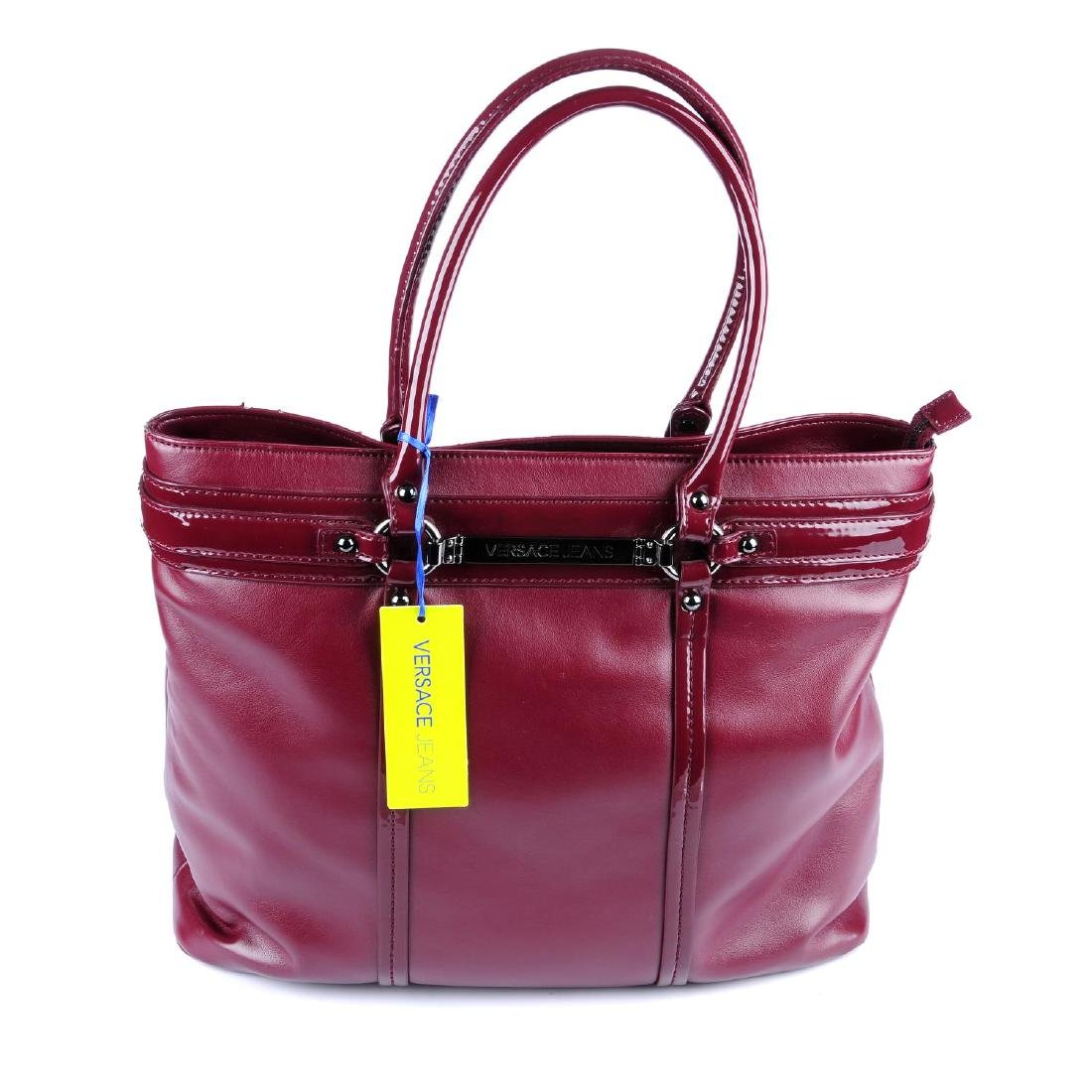 VERSACE JEANS - a burgundy handbag. Crafted from soft