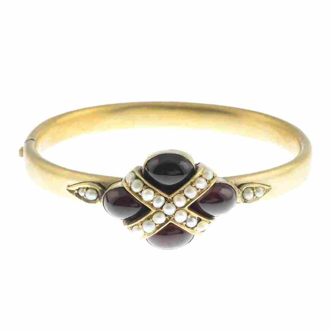 A late Victorian gold garnet and split pearl bangle.