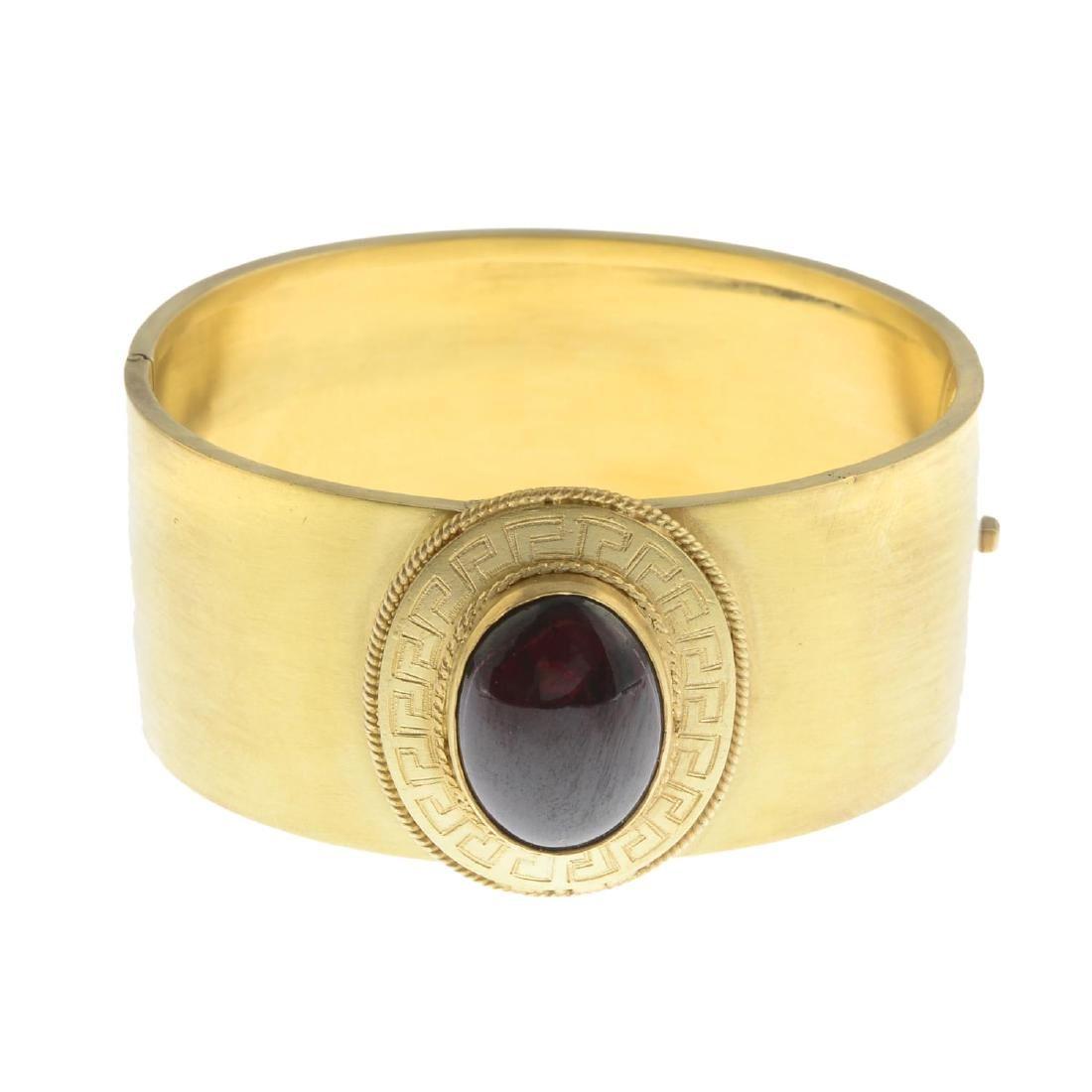 A late Victorian gold garnet bangle. Designed as an