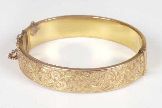 1004: 9ct gold hinged hollow bangle with scro