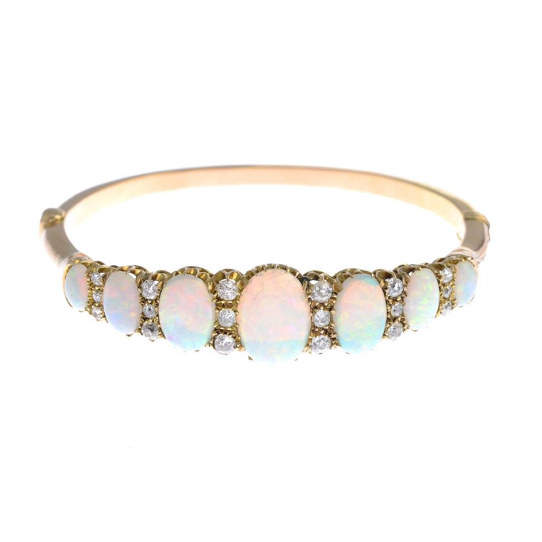 A late Victorian 18ct gold opal and diamond bangle. The