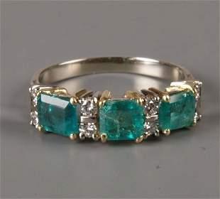 Emerald and diamond half hoop ring set with three p