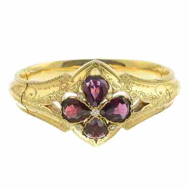 A late Victorian gold garnet and diamond bangle.