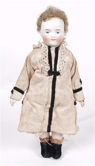 A small bisque doll, modelled as an infa