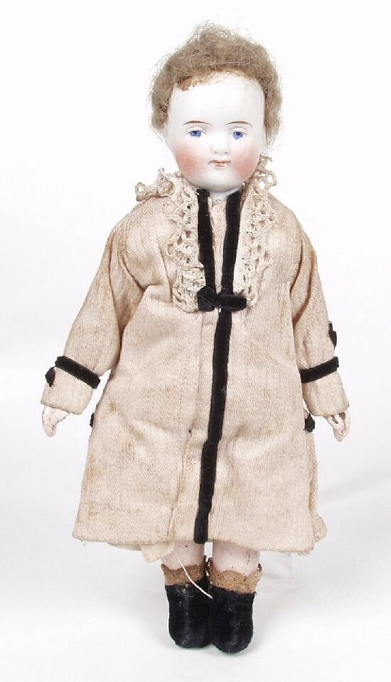 17: A small bisque doll,  modelled as an infa