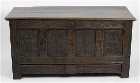An antique oak coffer the hinged two plank top with