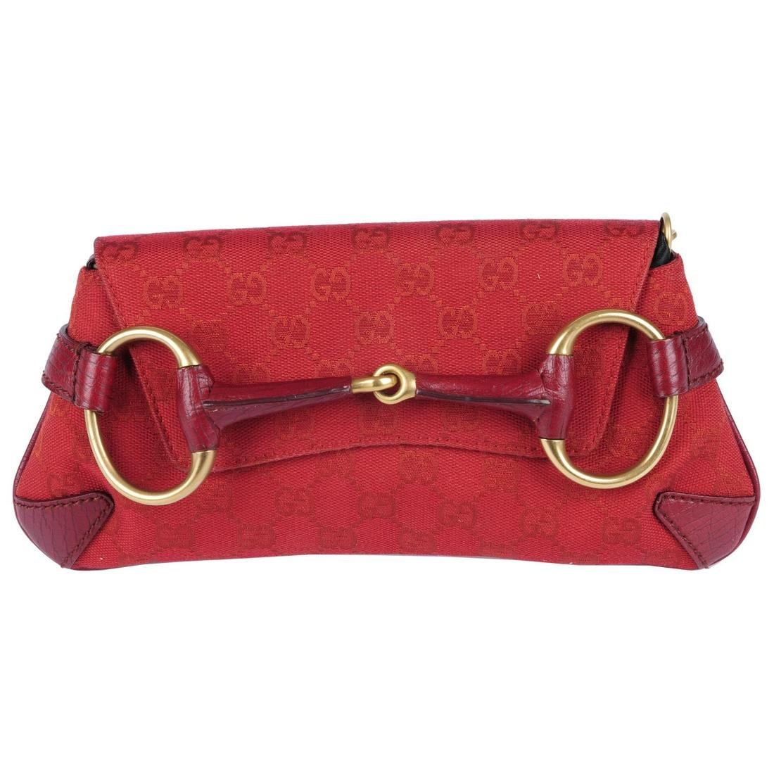 GUCCI - a red canvas Horsebit clutch. Designed with