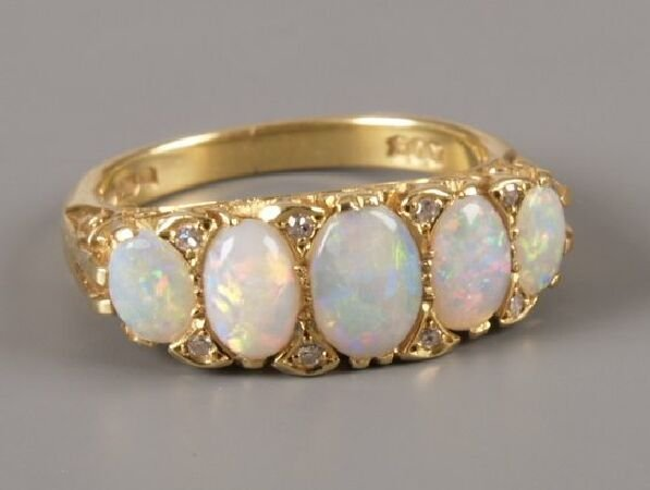 20: 18ct gold five stone opal set ring with eight small