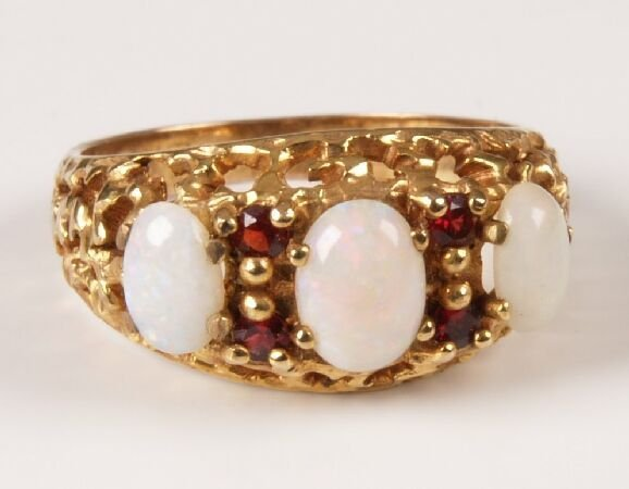 24: 9ct gold ring set with three oval cut opals and gar