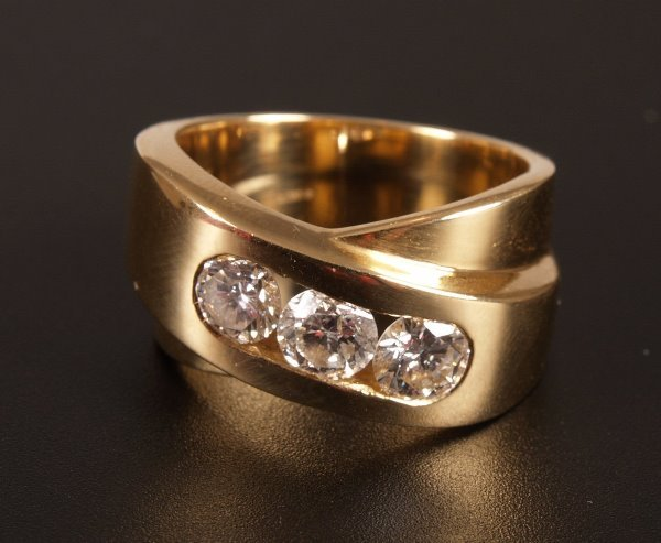 18: 18ct yellow gold channel set three stone round bril