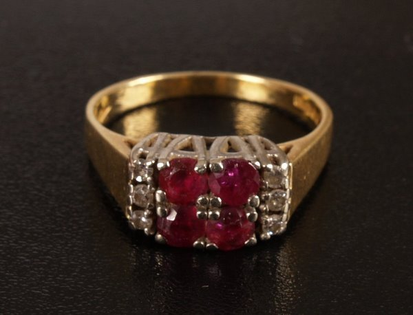 24: 18ct gold ruby and diamond set ring, set a central