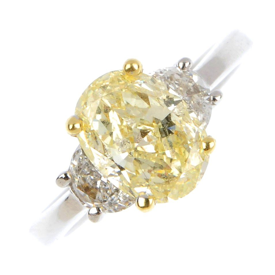 15: A diamond three-stone ring. The oval-shape yellow d
