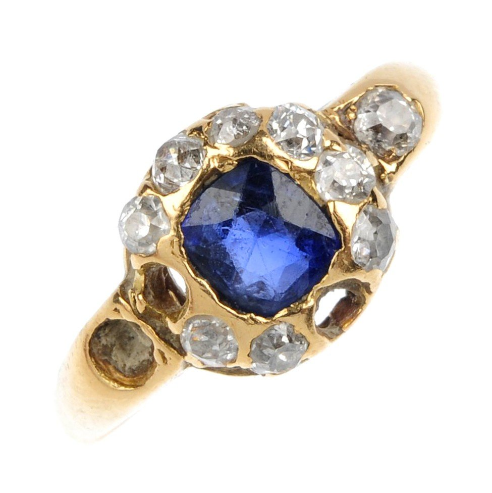19: A sapphire and diamond cluster ring. The oval-shape