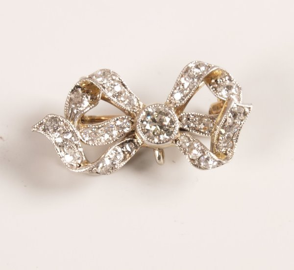 1014: An all diamond ribbon bow brooch with central old
