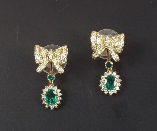 1016: A pair of oval emerald and diamond clus