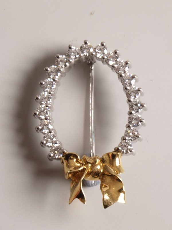 13: 18ct gold ribbon bow brooch with a circlet of claw