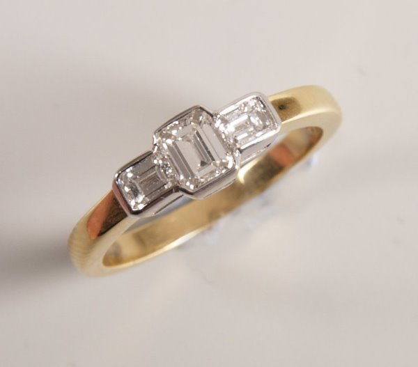 488: 18ct gold mounted three stone emerald cut diamond