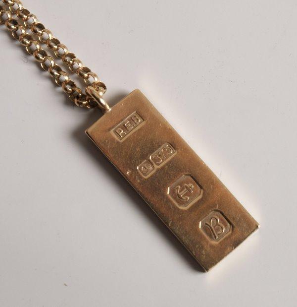1022: 9ct yellow gold ingot pendant suspended on 9ct go