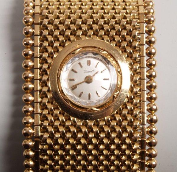 3020:  DERMONT - a ladies 18ct gold wide cuff style wat